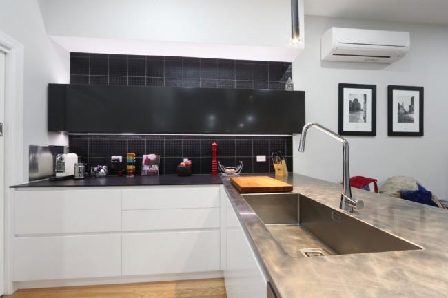 Сочетание металлической и черной матовой столешницы и контрастных оттенков в современном оформлении малогабаритной кухни