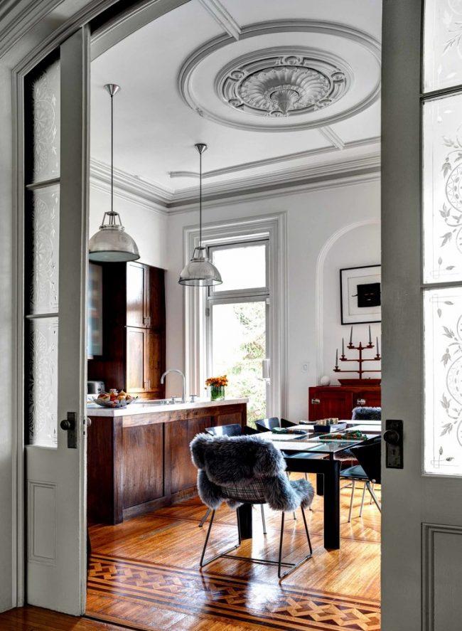 Просторная кухня с потолком, украшенным лепниной и галтелями