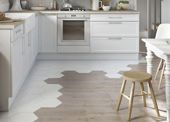 Необычное решение для зонирования пространства небольшой кухни: комбинирование белой шестиугольной плитки в рабочей зоне со светлой, имитирующей натуральное дерево, в обеденной