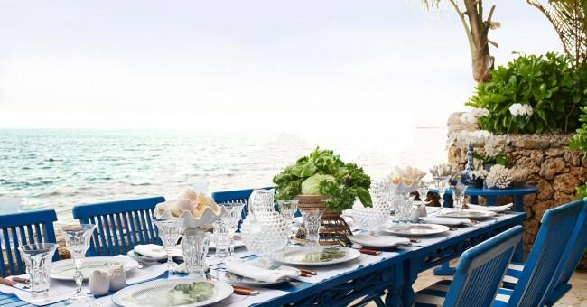 Нейтральный, но свежо и элегантно выглядящий микс для стола с пляжным оформлением: приборы с деревянными ручками, посуда из чистого бесцветного стекла и декор из свежей сочной зелени