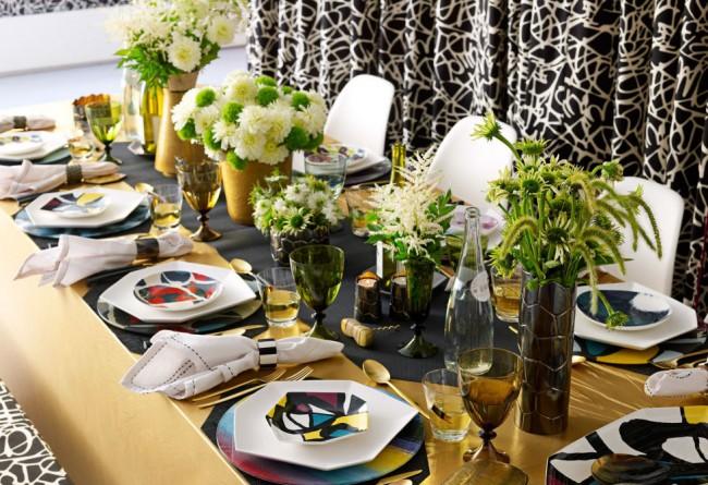 Геометричная форма ярко раскрашенной посуды и букеты полевых цветов в центре стола