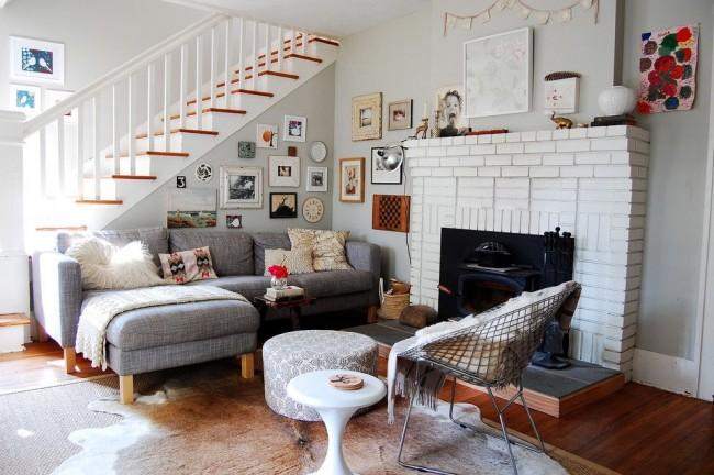 Колоритная гостиная в скандинавском стиле с объемным кирпичным камином, обилием текстиля и настенных картин