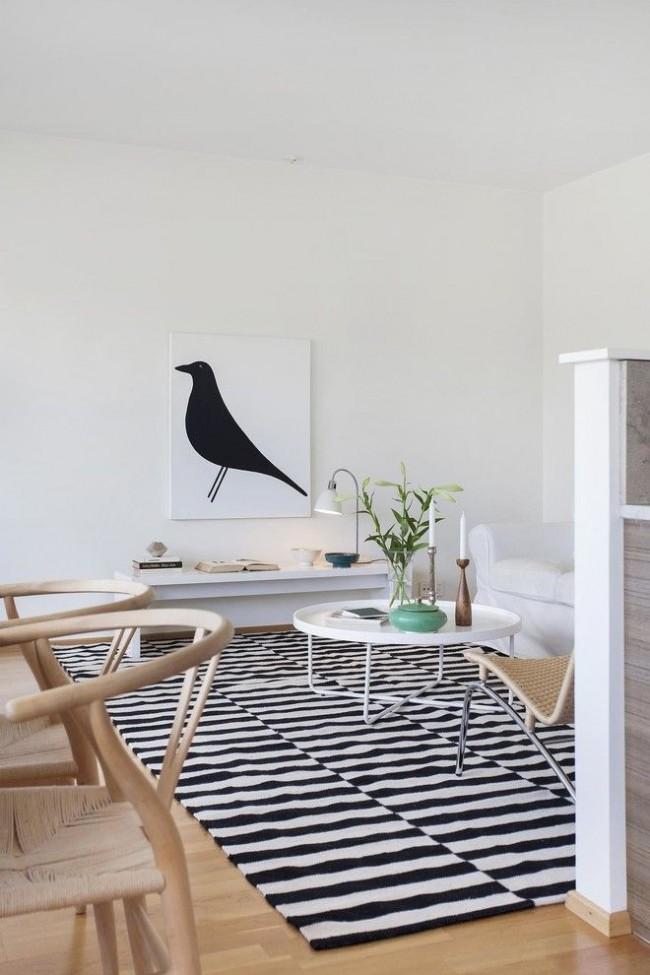 Выдержанная цветовая гамма в скандинавском интерьере в сочетании с плетеными креслами, аксессуарами и современным изобразительным искусством