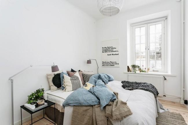 Белые стены, деревянный пол, окно без занавесок для лучшего проникновения света, искусственные источники освещения и обилие натуральных текстильных материалов – это все в скандинавском духе