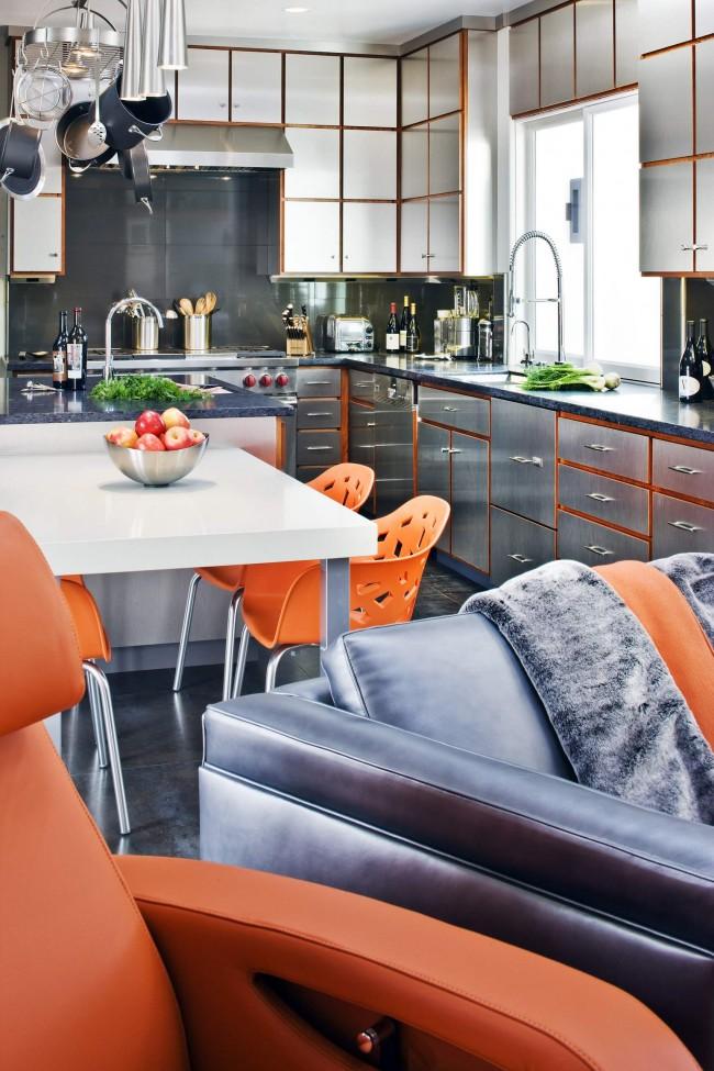 Оранжевый цвет объединяет пространство этой квартиры: он присутствует и на поверхностях шкафов, в оттенке лакированной древесины, и в обивке мягкой мебели, и ярких дизайнерских пластиковых стульях