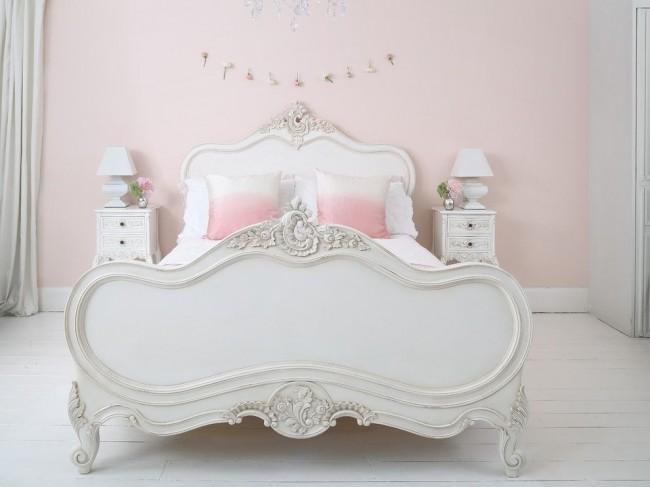 Белая спальня в стиле прованс с акцентами розового цвета: бледно-розовые обои, бело-розовый градиент на подушках, чайные розы