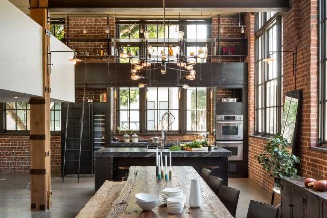 Характерная кухня в стиле лофт с обилием кирпича, дерева и металла в оформлении. Лампы Эдисона в объединенных трековых конструкциях и настенных светильниках подчеркивают общую тематику