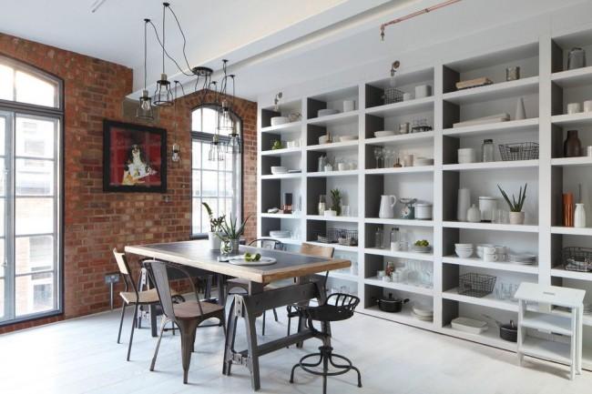 Столовая комната в стиле лофт с подвесными светильниками оригинальной конструкции и встроенными в стеллаж светильниками без плафонов