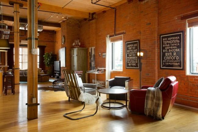Современная квартире в стиле лофт со смешанным освещением, диктующим зоны помещения без перегородок. Круглый журнальный стол, четыре разнообразных кресла и грубый металлический напольный светильник образуют зону для чтения