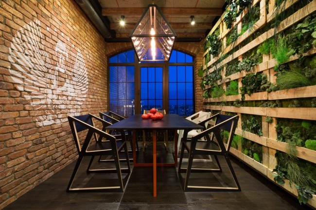 Лаконичная столовая в стиле лофт от группы дизайнеров MARTIN architects: кирпичная стена с противоположной растительной, черный пол, мебель в стиле минимализм, геометрическая осветительная конструкция