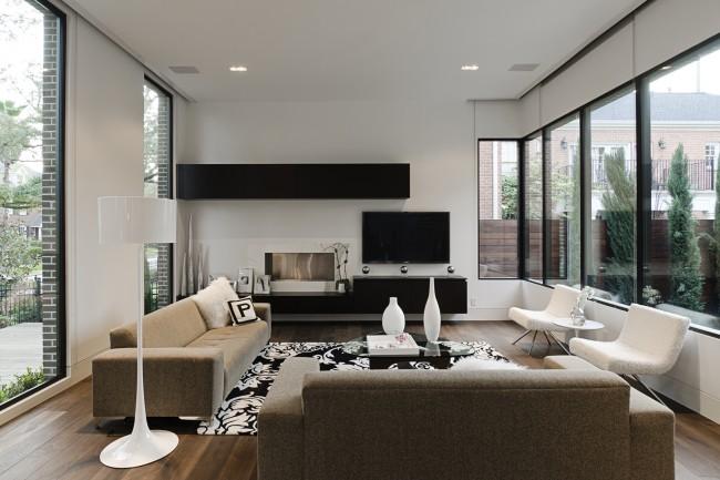 Интересное решение для заполнения стены большой гостиной частного дома: аккуратная модульная стенка подчеркивает настроение комнаты