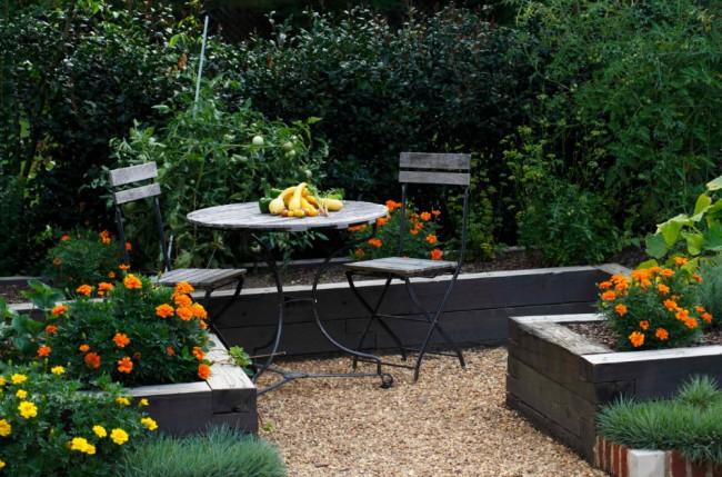 Уютное место для посиделок в небольшом саду, обилие зелени обеспечивает спокойное хорошее настроение