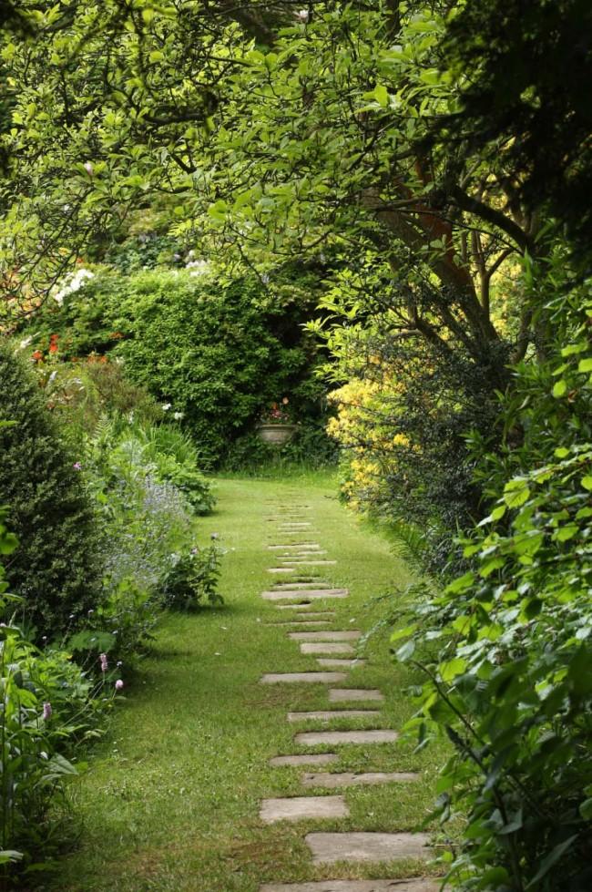 Минималистическая тропинка из небольших плит в сочном, зеленом саду