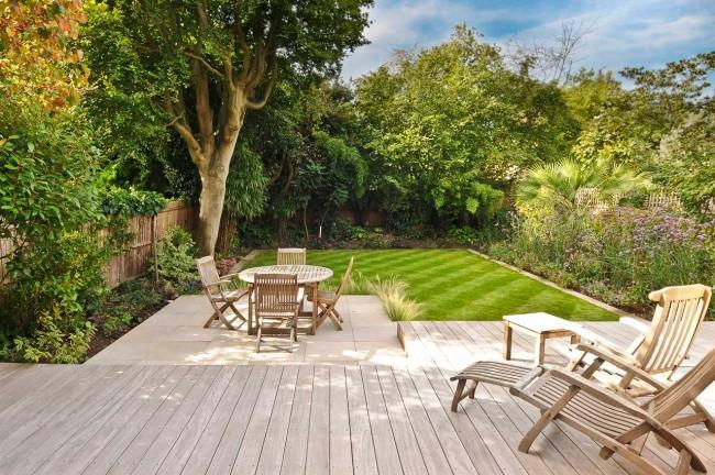 Широкое пространство сада с большой зоной отдыха и ухоженным необычным газоном