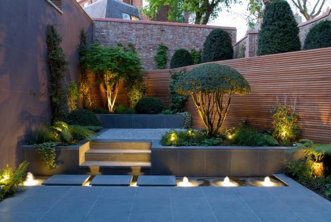 Интересная многоярусная конструкция в саду, оснащенная точечным освещением и подсветкой ступенек