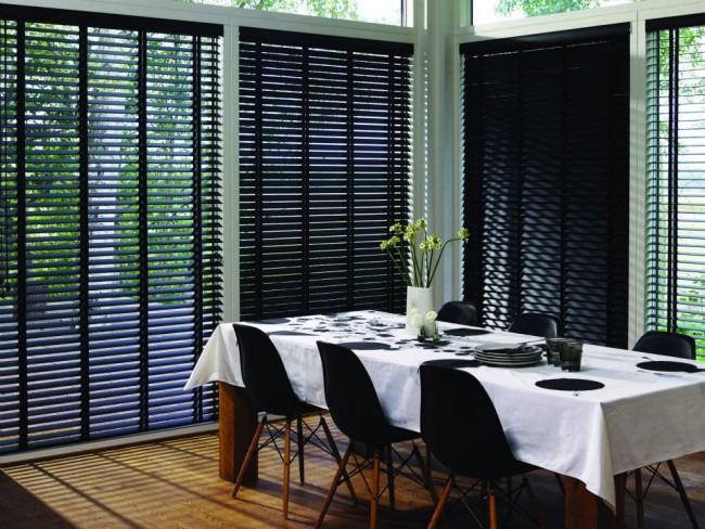 Черные жалюзи в обеденной зоне кухни частного дома регулируют количество попадания света в комнату