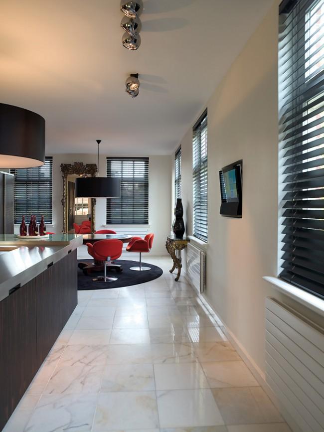 Темные жалюзи на кухне-студии - один из цветовых акцентов комнаты, где интерьер построен на контрастных играх цветов