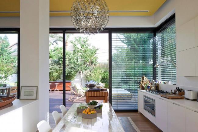 Необычные жалюзи на кухне-студии в светлых тонах с акцентами на деревянных элементах интерьера и ярко-желтом потолке в частном доме