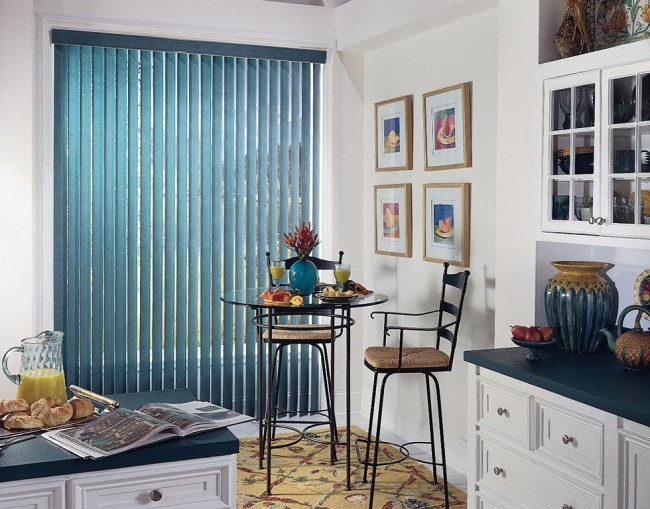 Компактная кухня-студия в светлых тонах с акцентами на элементах декора в цвете морской волны. Вертикальные жалюзи визуально вытягивают комнату, увеличивая ее пространство