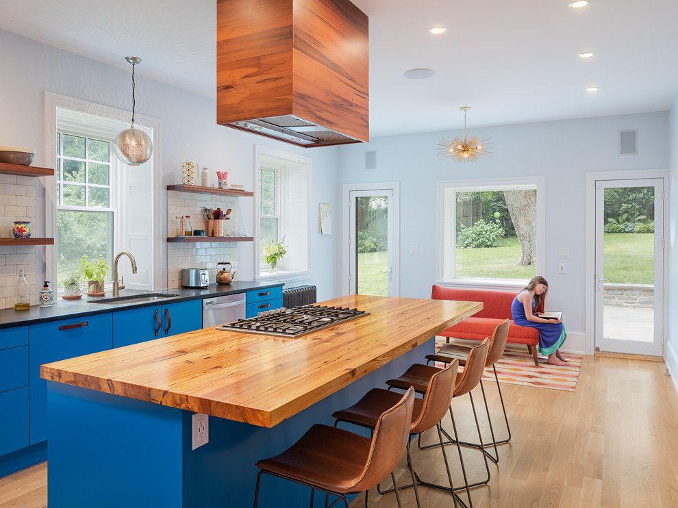 Ярко-голубая мебель и белые стены на кухне частного дома