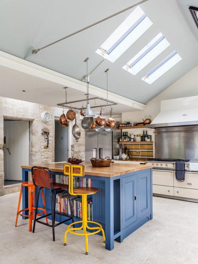 Нестандартные яркие стулья хорошо смотрятся в оформлении бело-голубой кухни в стиле лофт