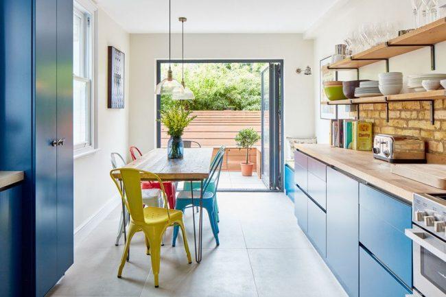 Просторная светлая кухня с голубыми фасадами, яркими стульями и кирпичным фартуком