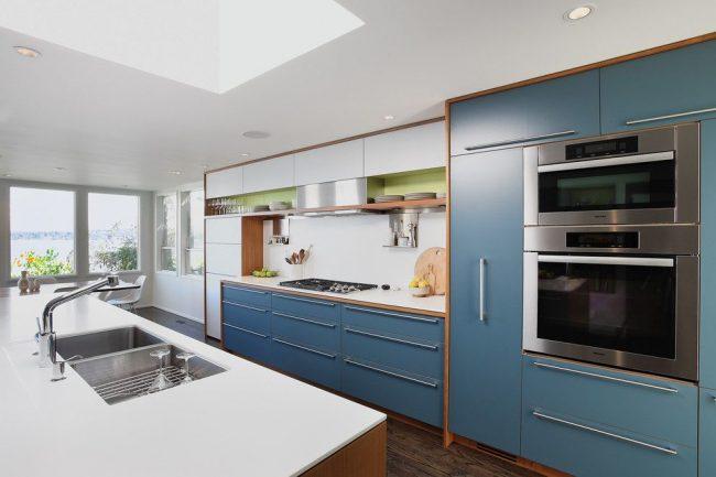 Спокойный голубой цвет в сочетании с преобладающим белым в интерьере просторной кухни