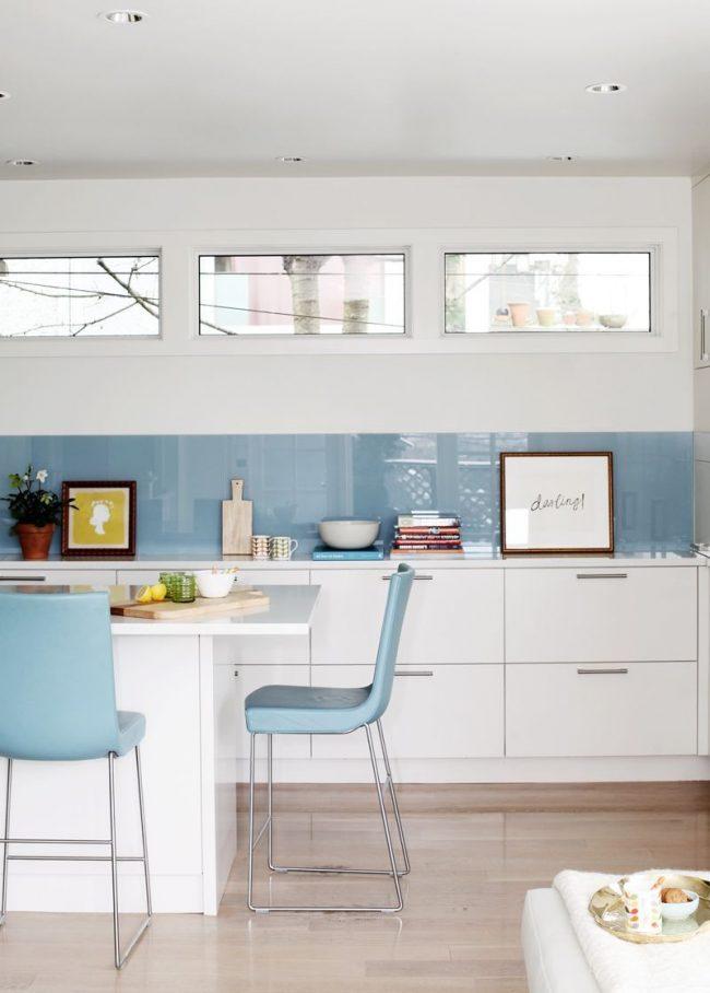 Бело голубая кухня: узкий голубой фартук и голубые стулья удачно освежают белый интерьер кухни