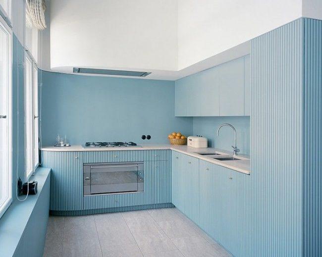 Г-образная кухня с голубой мебелью и белым потолком