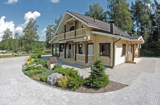 Небольшой брусчатый дом светло-бежевого цвета