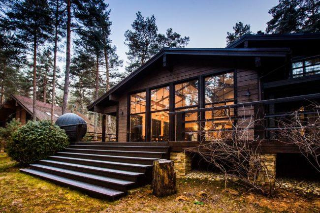 Дом из темного бруса смотрится достаточно стильно и красиво