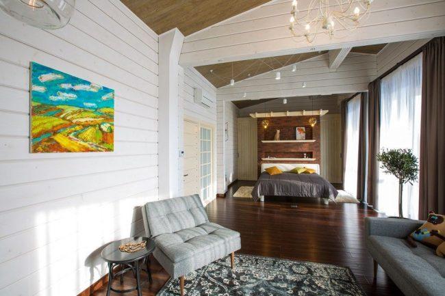 Просторная и уютная спальня частного дома из бруса в мансардном помещении