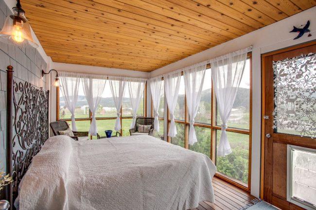 Круглый карниз с легкими занавесками на кулиске в спальне стиле кантри