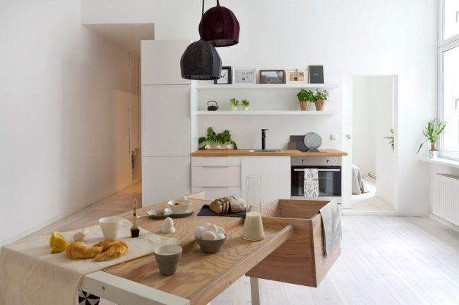 Маленькие картинки, расположенные на верхней полке хорошо дополняют интерьер кухни в скандинавском стиле