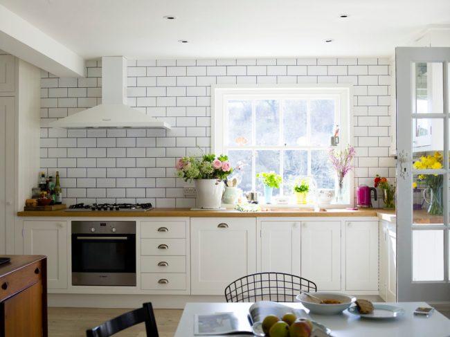 Стильная кухня белого цвета со множеством цветов в стиле кантри