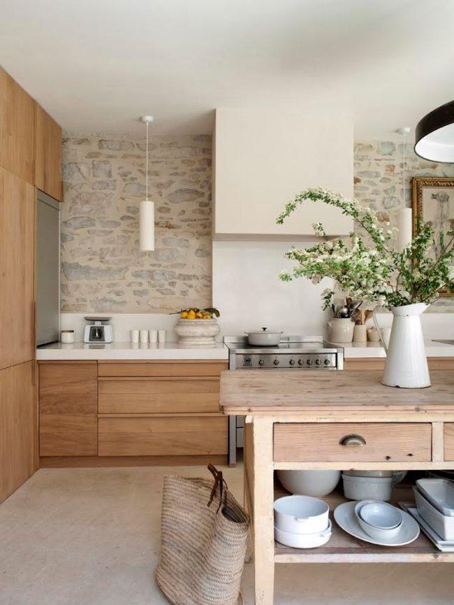 Деревянный стол с открытыми полками и каменная стенка на кухне в стиле кантри