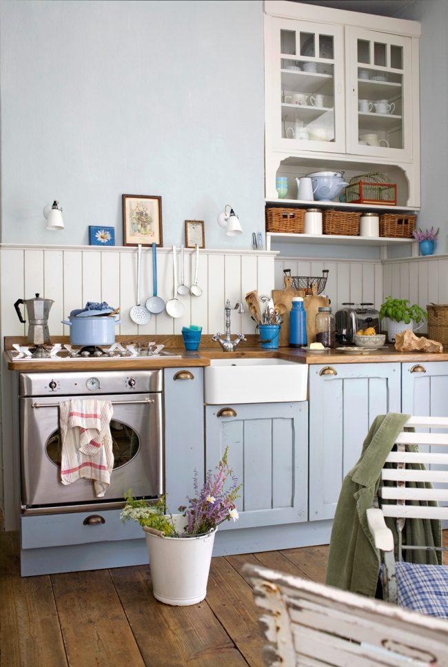 Голубая мебель, соломенные корзинки и эмалированная посуда на кухне в стиле кантри