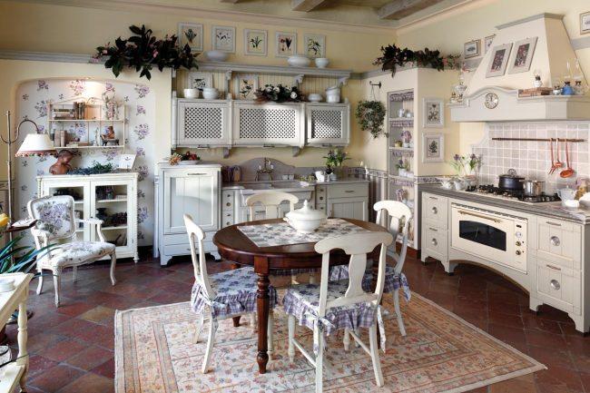 Кухня в стиле прованс с деревянной резной мебелью и цветочным рисунком на стенах и седушках стульев