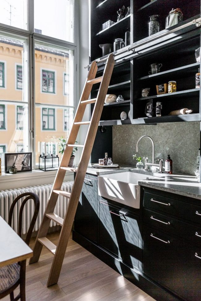 Даже такой элемент как стремянка может стать декоративным элементом кухни с высокими потолками и полками