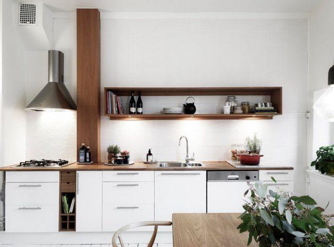 Кухня белого цвета с небольшими коричневыми вставками мебели - это стандартное решение для скандинавского стиля