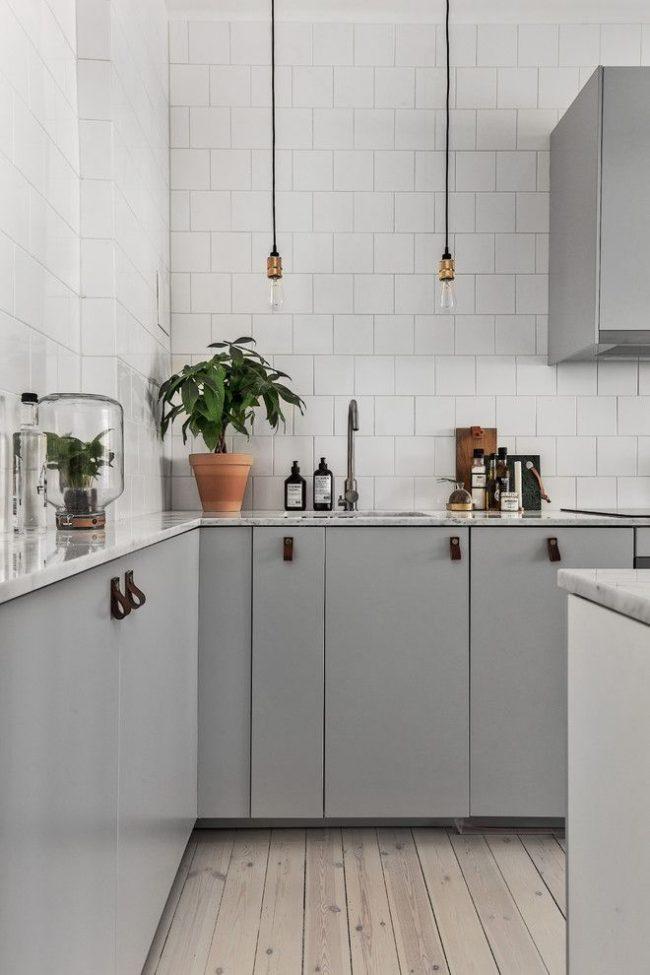Нестандартные мягкие ручки на дверцах шкафчиков и лампочки без плафонов, как элемент декора кухни в скандинавском стиле