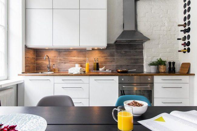 Стильная кухня в скандинавском стиле с бело-серой мебелью и белой кирпичной стенкой