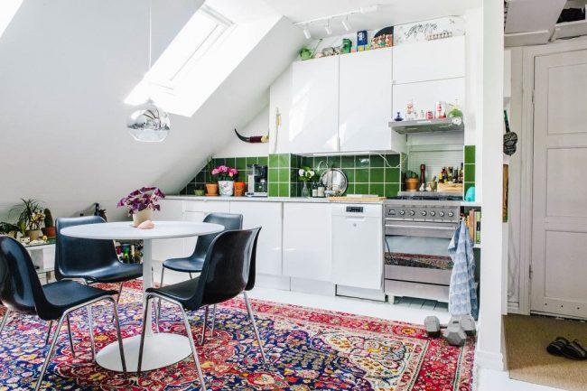 Фартук из зеленой плитки и яркий ковер на полу добавят ярких красок в стандартный скандинавский стиль кухни