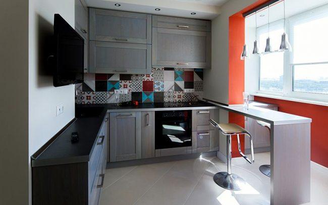 Контраст серой кухни и небольшого балкона в оранжевом цвете