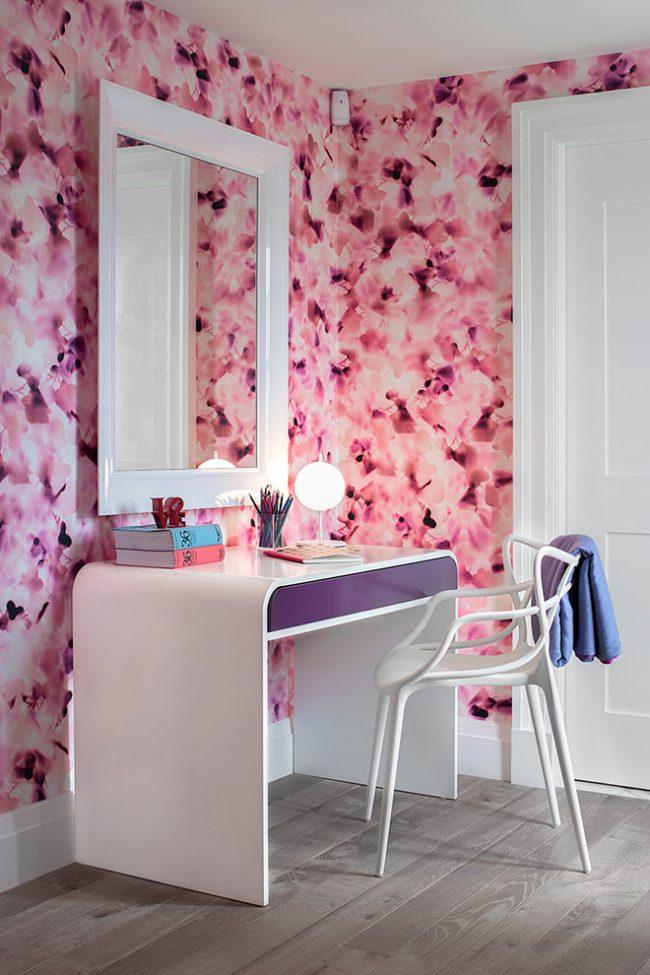Гармоничное сочетание изящного письменного стола и ярких обоев в интерьере комнаты для девочки