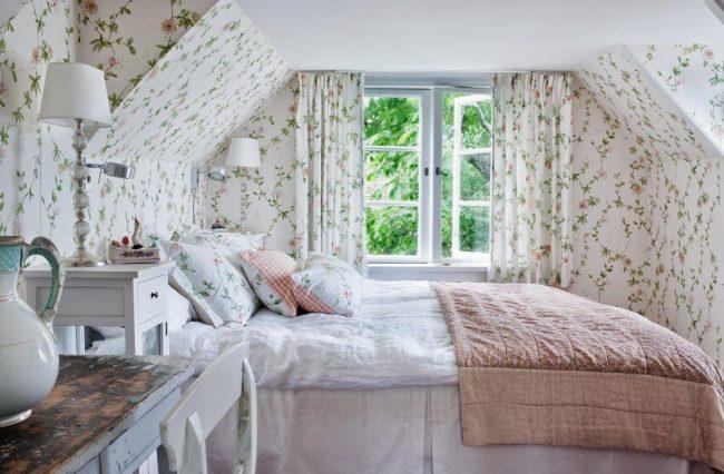 Светлые романтичные обои с аналогичным рисунком на шторах в мансардной спальне в прованском стиле
