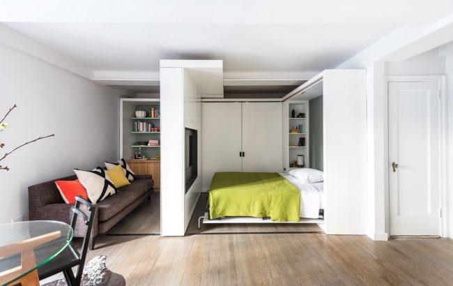 Гипсокартонная стенка с нишей под телевизор - это хороший вариант разделения зоны спальни и гостиной для однокомнатной квартиры