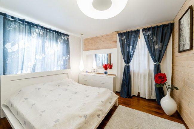 Коричневый паркет в сочетании со светлой вагонкой и белым потолком в спальне частного дома