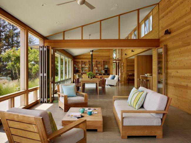 Панорамные окна и светлое дерево в обшивке гостиной частного дома