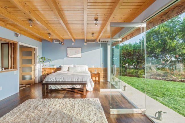 Отделка деревянного дома внутри: темный паркет в спальне частного дома